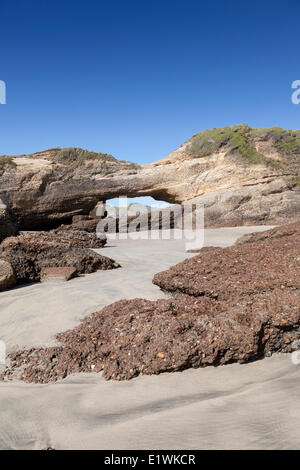 Rock archway on Wharariki Beach on the South Island of New Zealand at low-tide - Stock Photo
