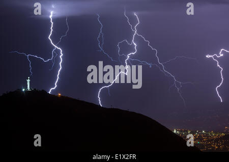 Lightning during a thunderstorm over the city of Cochabamba, Bolivia. El Cristo is in the foreground. - Stock Photo