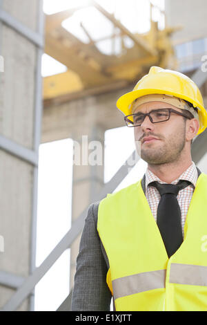 Young male engineer wearing hard hat looking away at construction site - Stock Photo