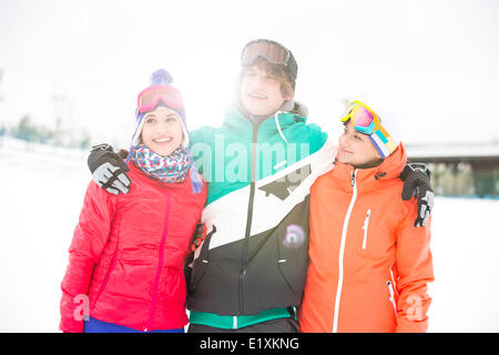 Young man with female friends standing arm around in snow - Stock Photo