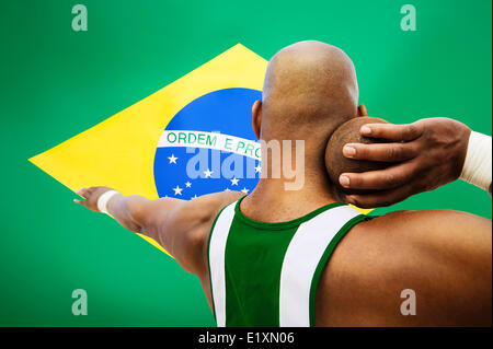 Rear view of male shot putter aiming against Brazilian flag - Stock Photo