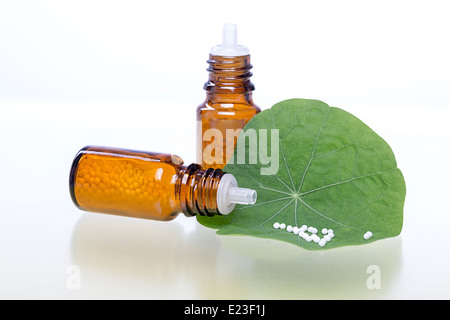 two bottles with homeopathy globules and green leaf. - Stock Photo