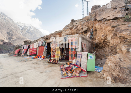 Shops on a track selling rugs and other souvenirs in the High Atlas Mountains, Morocco - Stock Photo