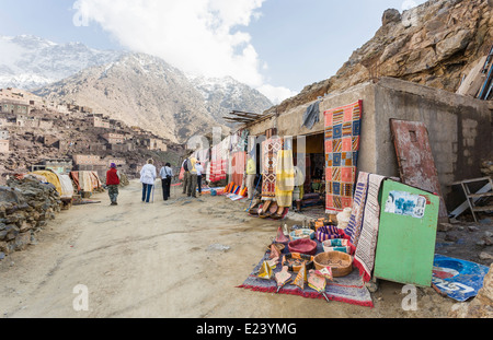 Shops on a track selling rugs and other souvenirs in the High Atlas Mountains, Morocco to passing walkers and trekkers - Stock Photo