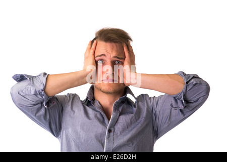 Desperate, upset young man with hands on his face and looking at camera - Stock Photo