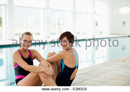 Portrait of smiling women in bathing suits at poolside - Stock Photo