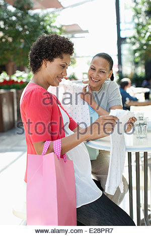 Pregnant woman and friend looking at baby clothes - Stock Photo