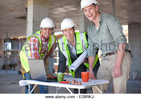 Construction workers working together on construction site - Stock Photo