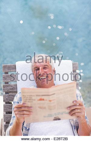 Senior man reading newspaper at poolside - Stock Photo