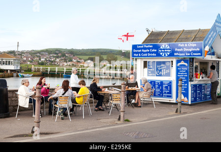 People eating fish and chips at a fish and chip shop, West Bay, Bridport Harbour, Dorset coast, England UK - Stock Photo
