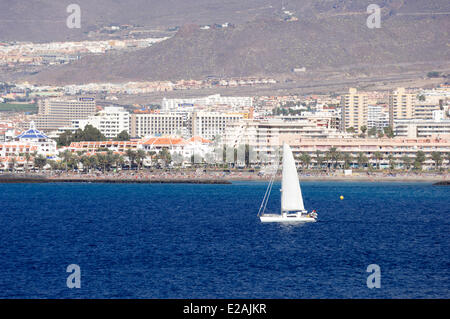 Spain, Canary Islands, Tenerife, sailboat in front Playa de Las Americas buildings and hotels - Stock Photo