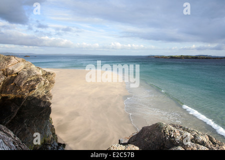 A deserted Irish beach on the Island of Inishbofin, in the West of Ireland with waves breaking on the golden sandy - Stock Photo
