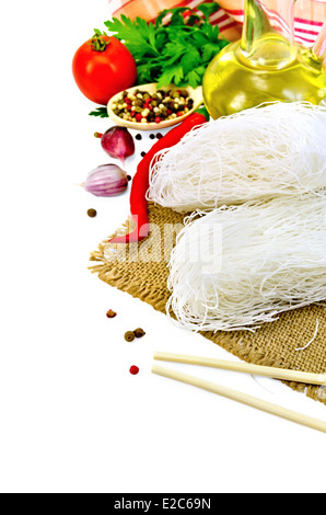 Rice noodles thin, tomatoes, different peppers, chopsticks, garlic, parsley, oil, sacking isolated on white background - Stock Photo