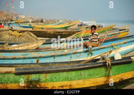 India Odisha state Puri small boy on local colorful fishing boats - Stock Photo