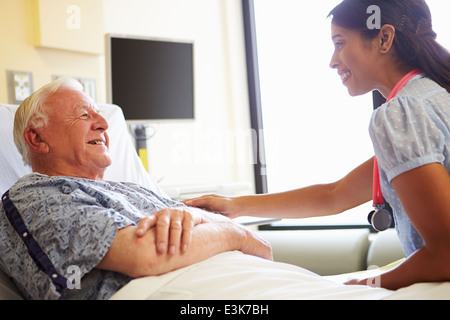 Female Doctor Talking To Senior Man In Hospital Room - Stock Photo