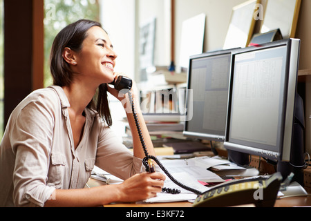 Female Architect Working At Desk On Computer - Stock Photo