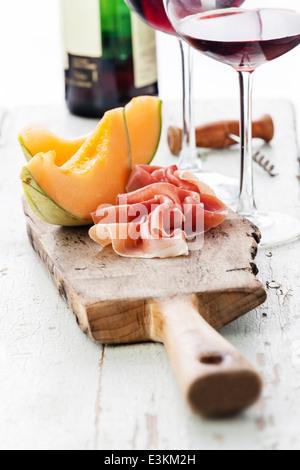 Slices of melon cantaloupe with prosciutto ham - Stock Photo