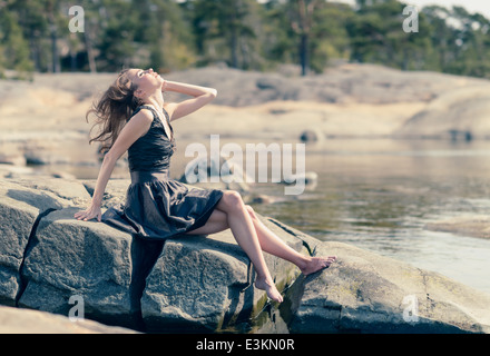 Beautiful young woman sits on the rock, sunny day on beach - Stock Photo