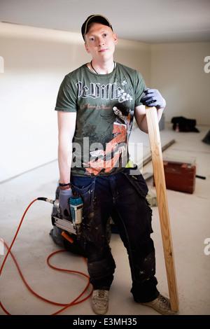 Full length portrait of confident carpenter standing at site - Stock Photo