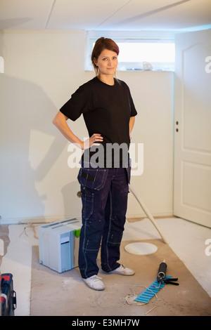 Portrait of confident female carpenter standing at site - Stock Photo