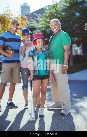 Portrait of happy multi-generation family playing baseball in street - Stock Photo