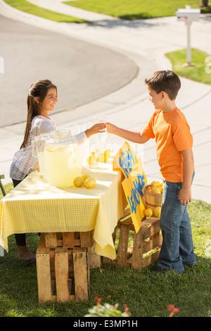 Boy buying lemonade at lemonade stand - Stock Photo