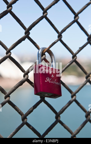 Love padlocks chainlink fence against beach - Stock Photo