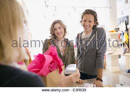 Couple using credit card reader in shop - Stock Photo