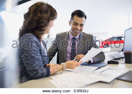 Salesman and woman finalizing paperwork in car dealership - Stock Photo