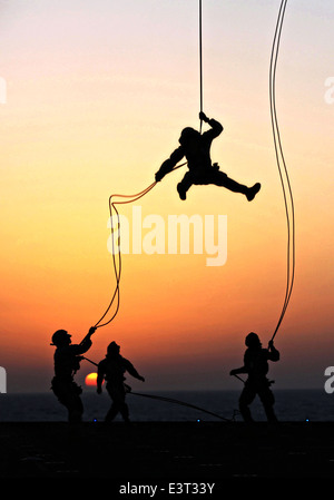 US Marines with Battalion Landing Team, 22nd Marine Expeditionary Unit, rappel out of a CH-53E Super Stallion helicopter - Stock Photo