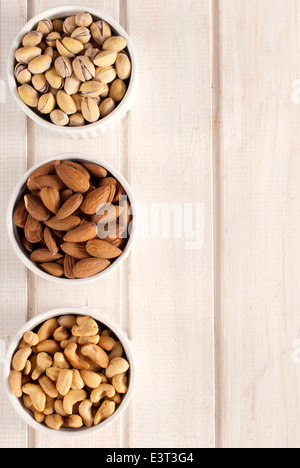 Nuts fruit in the bowls from above on wooden table and blank space on right side - Stock Photo