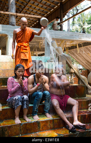 Ceremony of Buddhist Monk blessing family in Angkor Cambodia - Stock Photo
