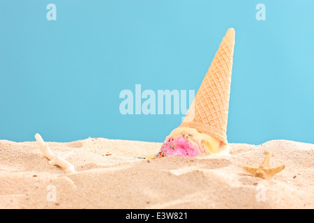 Studio shot of an ice cream splashed on sand - Stock Photo