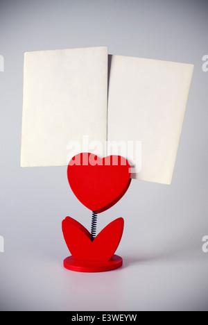 heart-shaped photo holder holding two blank photos - Stock Photo