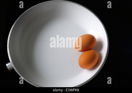 Two raw eggs in a white frying pan - Stock Photo