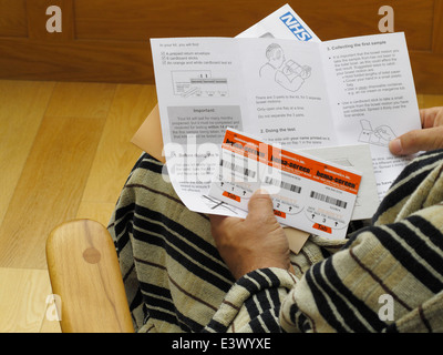 Slide test for faecal occult blood mass screening for bowel cancer in UK.  senior over 60s man reading instructions - Stock Photo