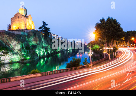 Metekhi church and Avlabari quarter iluminated at dusk with traffic motion trails in foreground, Tbilisi, Georgia - Stock Photo