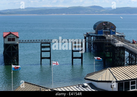 mumbles lifeboat stations old (left) and new (right) with flags flying blue sea and sky across Swansea bay - Stock Photo