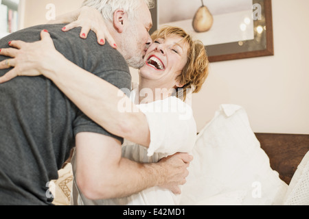 Couple hugging, mature woman laughing - Stock Photo