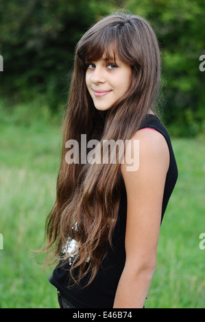 girl teen teenager transition age 13 14 15 years brunette hair long dark nature park open air beautiful portrait - Stock Photo