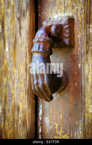 Close up on a rusty iron door knocker in a decaped old wooden door - Stock Photo