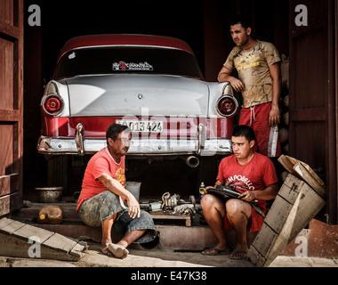 Three man fixing an oldtimer car, Trinidad, Cuba - Stock Photo