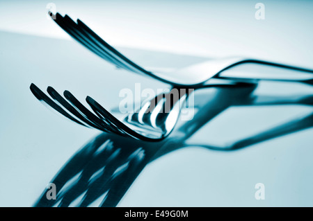 closeup of some forks on a reflecting surface - Stock Photo
