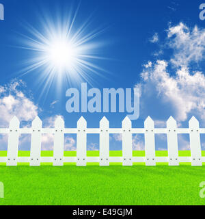 white fence on a summer lawn in a sun day - Stock Photo