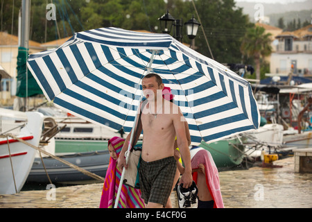 A family use a large beach umbrella to escape torrential rain and hail from a thunderstorm in Sivota, Greece. - Stock Photo