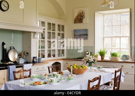Mouseman chairs by Thompson of Kilburn and place around a dining table in a country style kitchen. - Stock Photo