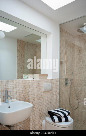 Contemporary bathroom with tiled walls and walk-in shower - Stock Photo