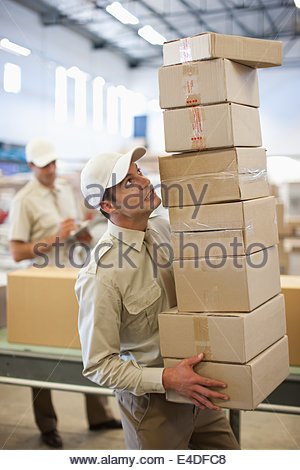 Worker carrying stack of boxes in shipping area - Stock Photo