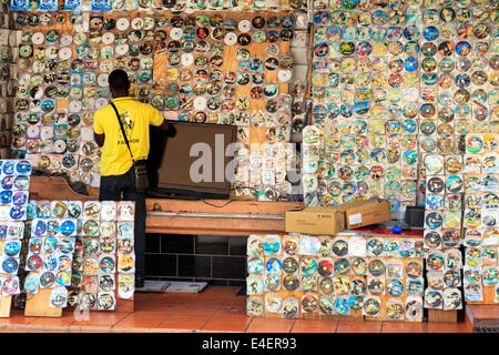 Man selling pirated DVDs and CDs from a street stall, St George, Grenada, West Indies. - Stock Photo