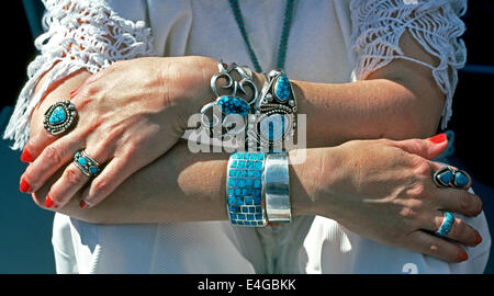 A woman displays her pawn jewelry collection of turquoise and silver rings and bracelets handcrafted by Navajo Indians - Stock Photo